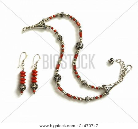 Unique bracelet with earrings made of silver and coral beads, isolated on white. Handicraft from Croatia.