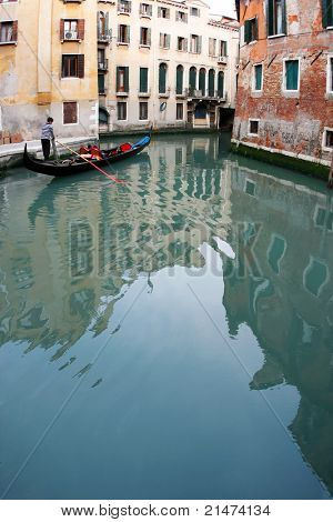 Couple having a romantic ride down a canal in a gondola (Venice, Italy)