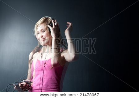 Music please! - Portrait of a pretty young woman/teenager listening to music on her hi-end headphones, enjoying the groove (multiple exposure shot)