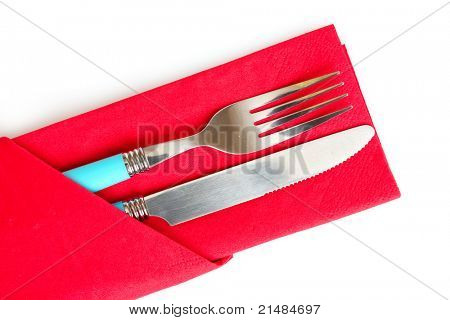 knife and fork in a red cloth, isolated on white