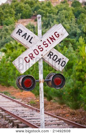 Railroad Crossing sign with tracks & trees in the distance. Shallow focus on the sign.