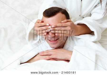 man with eyes closed by his girlfriend's hands
