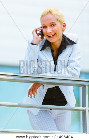 Smiling modern business woman leaning on railing at office building and talking on mobile