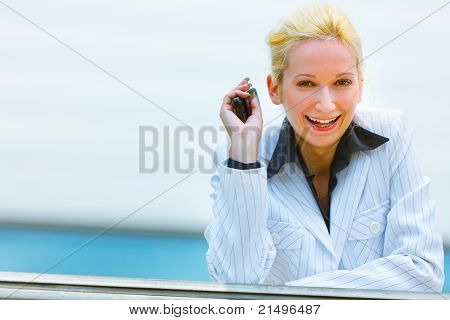 Smiling modern business woman with mobile in hand leaning on railing at office building