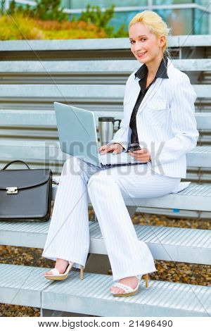 Smiling modern business woman sitting on stairs at office building and working on laptop