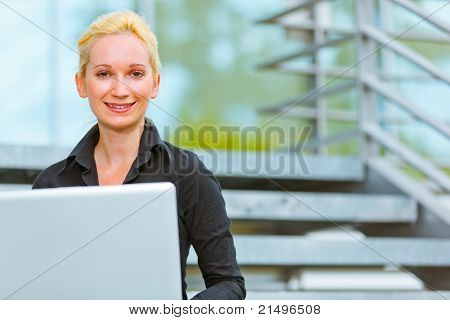 Pleased modern business woman sitting on stairs at office building and using laptop