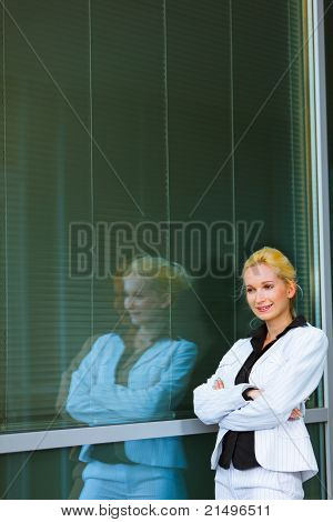 Pensive modern business woman standing near office building