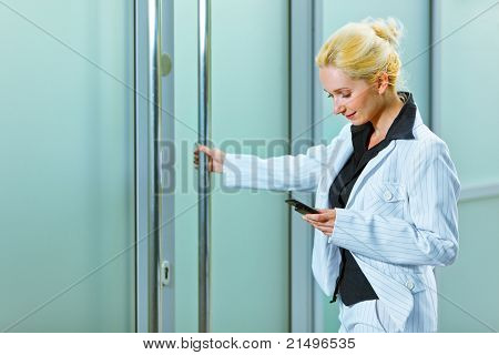 Smiling modern business woman with mobile entering office building