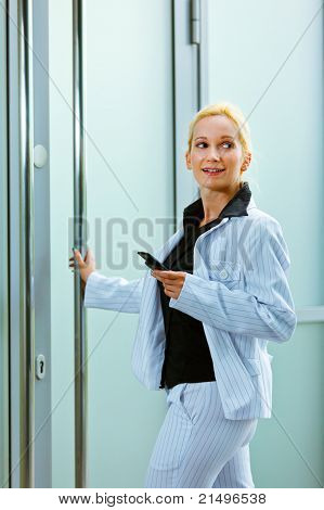 Smiling modern business woman entering office building holding mobile in hand