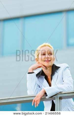 Thinking about something modern business woman leaning on railing at office building