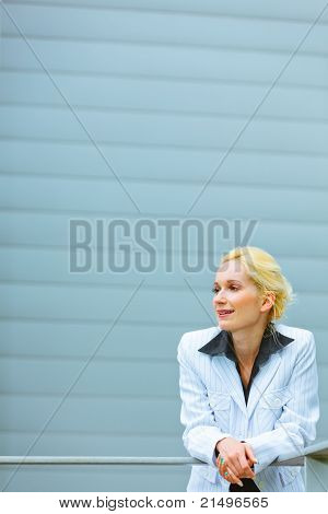 Thoughtful modern business woman leaning on railing at office building and looking at copyspace