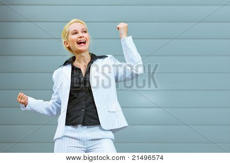 Pleased modern business woman standing at office building and rejoicing her success