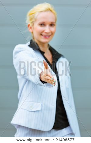 Standing at office building modern business woman stretches out hand for handshake