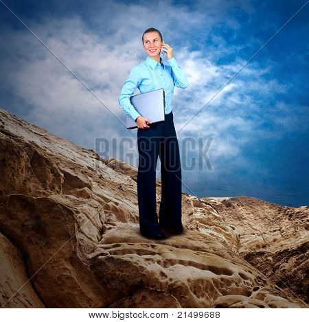 Happy Businesswoman standing with laptop on the mountain under blue sky