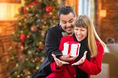 Mixed Race Couple Sharing Christmas In Front of Decorated Tree. poster