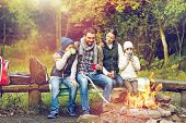 camping, travel, tourism and people concept - happy family sitting on bench and drinking hot tea fro poster