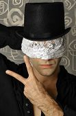 foto of illuminati  - Fantastical stylized portrait of mystery man in top hat with lace blindfold making hand gesture - JPG