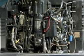 foto of outboard engine  - The top part of an outboard motor is opened up and exposed for repair - JPG