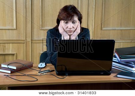 Business Woman Thoughtfully Looks At The Laptop In An Office