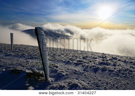 evening sunshine and inversion clouds on mountains with frostbitten tourist rod marks