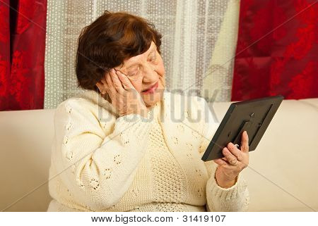 Sad Elderly Woman Looking At Photo Frame