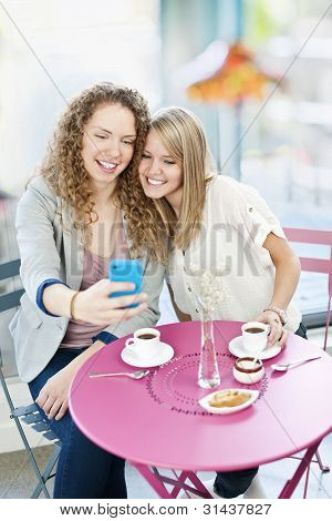 Woman Showing Phone To Friend