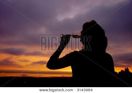 Beautiful Middle Aged Woman Drinking A Glass Of White Wine On Her Deck At Sunset