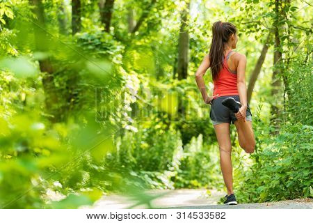 poster of Fit stretch woman stretching quad leg muscle standing getting ready to run jogging outside in summer