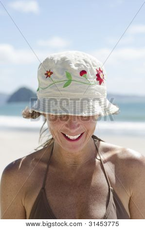 Happy laughing woman on beach wearing hat