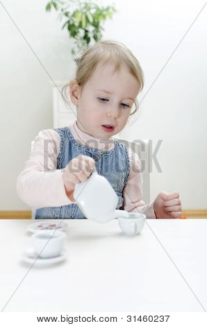 Cute Little Girl Drinks Tea At Home.
