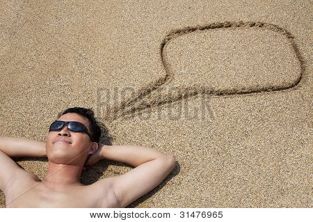 Smiling Young Man Lying On The Beach And Dialog Symbol