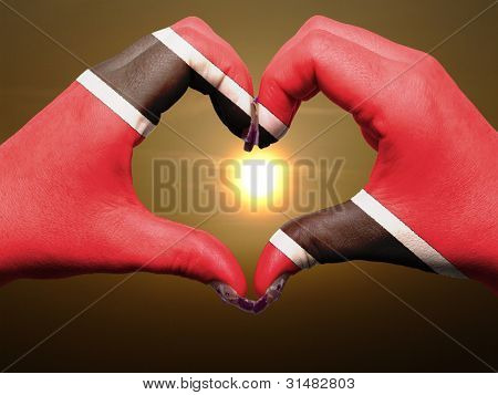 Heart And Love Gesture By Hands Colored In Trinidad Tobago Flag During Beautiful Sunrise For Tourism