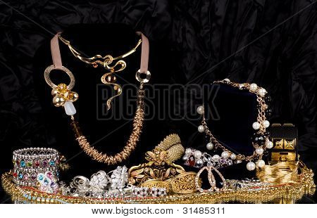 Gold jewelry (rings,earrings and necklaces)on a black background