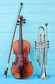 Musical Instruments Of Orchestra. Brown Violin, Bow And Trumpet On Blue Wooden Background, Vertical  poster