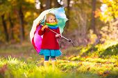 Kid With Umbrella Playing In Autumn Rain. poster