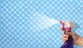 foto of house cleaning  - female hand spraying cleaning polish over a cloth background - JPG