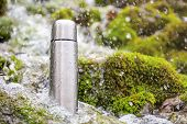 stock photo of drinking water  - Stainless steel thermos is in the turbulent river water - JPG