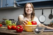 Young Cheerful Girl Prepares A Vegetarian Salad In The Kitchen, She Takes Out A Yellow Pepper From T poster