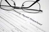 stock photo of payroll  - Close up of reading glasses on Biweekly payroll timesheet - JPG