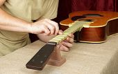 Musical Instrument Guitar Repair And Service - Worker Polishing Guitar Neck Frets Acoustic Guitar Sa poster