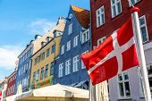 Copenhagen Iconic View. Denmark Flag Against Nyhavn Canal With Colorful Medieval Houses In The Cente poster