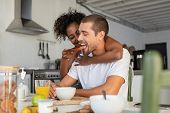 African american woman embracing from behind her boyfriend and feeding him with brown bread and jam. poster