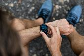Fit man checking smart watch wearable technology sport smartwatch on fitness run walk outside. Top v poster