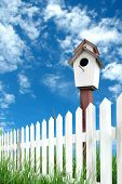 pic of bird fence  - white fence with bird house and blue sky - JPG