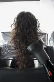 Brunette Woman Drying Her Hair At A Hairdresser poster