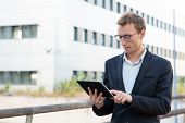 Positive Focused Professional Working On Tablet Outside. Young Business Man Standing Outside, Using  poster