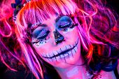 Close-up Portrait Of An Attractive Woman With Sugar Skull Makeup In Bright Blacklight Bodyart poster