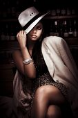 pic of titillation  - Stylish Trendy And Fashionable Female Model Wearing Slanting Hat And Coat Over A Elegant Evening Dress Inside A Dark Bar In A Depiction Of Dark Fashion - JPG