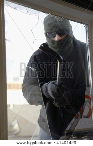 Thief in balaclava breaking glass of window to enter the house