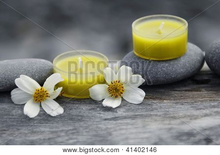 Still life with two yellow candle and two white flower,stone